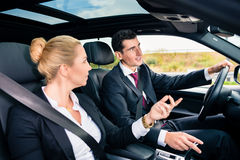Business couple in car travelling Stock Images