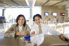 Business couple checking in at airport, businessman receiving boarding passes from check-in attendant, view from behind check-in d Royalty Free Stock Image