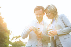 Business couple conversing while using cell phone on sunny day Royalty Free Stock Images