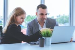 Business couple discussing on laptop screen, Coworker brainst. Business couple is discussing on laptop screen, Coworker brainstorming in office stock photography
