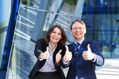 A business couple in formal clothes holding thumbs. A successful business couple in formal clothes holding thumbs up. The image is taken on a modern Royalty Free Stock Image