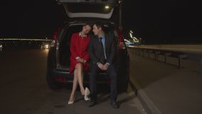 Business couple resting in car trunk at night stock video
