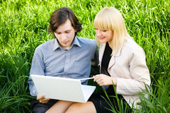 Business couple on the grass Royalty Free Stock Image