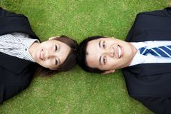 Business couple.happy  businessman and woman. Lay on the grass Stock Image