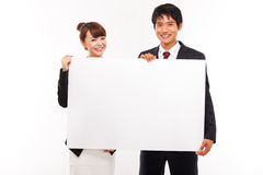 Business couple holding a add banner. Business couple holding a add banner isolated on white background Royalty Free Stock Images