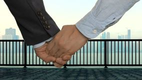 Business couple holding hands. River, quay with railings and downtown with skyscrapers. Business couple in formal wear holding hands. River, quay with railings stock footage