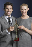 Business Couple Holding Trophy Royalty Free Stock Photos
