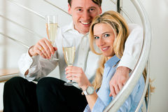 Business Couple at home with champagne. Business Couple - man and woman - at home with champagne sitting on stairs in their apartment Royalty Free Stock Photos