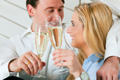 Business Couple at home with champagne. Business Couple - man and woman - at home with champagne sitting on stairs in their apartment Royalty Free Stock Photography