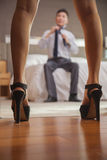 Business couple in hotel room, shot through legs of woman Royalty Free Stock Images