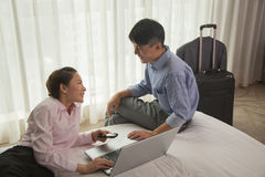 Business couple in hotel room, smiling and working on laptop Royalty Free Stock Photos