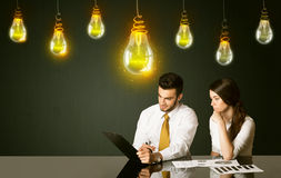 Business couple with idea bulbs Royalty Free Stock Images