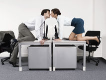 Business Couple Kissing Over Desks In Office Stock Photo