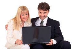 Business couple with laptop. Half body portrait of woman and middle aged businesspeople looking at laptop, isolated on white background Royalty Free Stock Image