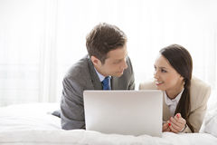 Business couple with laptop looking at each other in hotel room Stock Photos