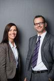 Business couple leaning against a wall Royalty Free Stock Images