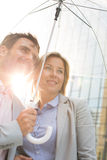 Business couple looking away while standing under umbrella on sunny day Stock Photography