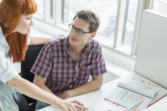 Business couple looking at each other while using laptop in creative office Royalty Free Stock Photos
