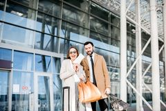 Business couple near the airport. Happy business couple in coats stading with tickets in front of the airport entrance Royalty Free Stock Photography