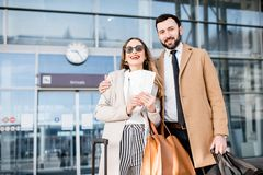 Business couple near the airport. Portrait of an elagant and happy business couple in coats stading with tickets in front of the airport entrance Royalty Free Stock Photos