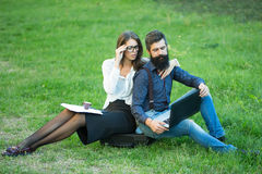 Business couple outdoor. Business young pair of slim women and men with long lush black beard with office devices of laptop glasses mobile phone paper folder and stock photography
