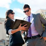 Business couple outdoors with catalog. Royalty Free Stock Photography