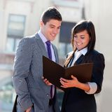 Business couple outdoors with files. Stock Photos