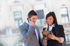 Business couple outdoors with tablet. Stock Photography