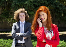 Business couple. Outside, using phone Royalty Free Stock Images