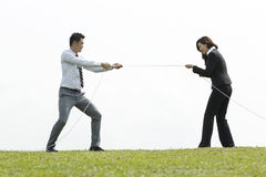 Business couple playing tug of war Stock Photography