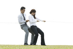 Business couple playing tug of war Stock Photo