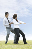 Business couple playing tug of war Stock Images