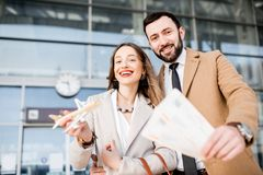 Business couple portrait near the airport. Portrait of a happy business couple in coats stading with tickets and toy airplane in front of the airport entrance Royalty Free Stock Photos