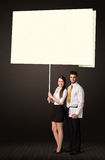 Business couple with post-it paper. Young business couple holding a big, white post-it paper Royalty Free Stock Photo