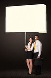 Business couple with post-it paper. Young business couple holding a big, white post-it paper Royalty Free Stock Photos