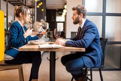Business couple at the restaurant. Caucasian business couple dressed strictly in the suits having discussion sitting together at the restaurant during the dinner royalty free stock photography