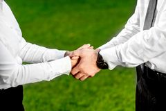 Business couple shaking hands outdoors Stock Images