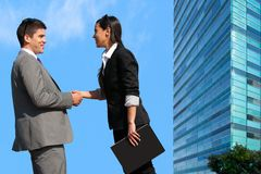 Business couple shaking hands over deal outdoors. royalty free stock images