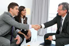 Business couple shaking hands with partner. royalty free stock images