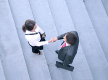 Business couple shaking hands together. A business couple is shaking hands in order to show success. Image taken on a stairway background Royalty Free Stock Photography