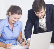 Business couple sign document. Business couple working on a laptop and sign document Royalty Free Stock Images