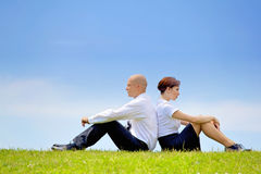Business couple sitting back to back on grass Stock Image