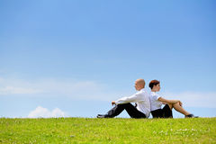 Business couple sitting back to back on grass Stock Photo