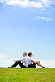 Business couple sitting back to back on grass Stock Images
