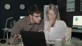 Business couple watching together financial report front computer in dark office stock video