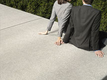 Business Couple Sitting On Wall Outdoors Royalty Free Stock Photos