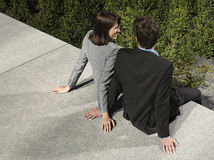 Business Couple Sitting On Wall Outdoors Royalty Free Stock Photo