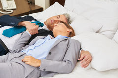 Business couple sleeping on bed in hotel Stock Image