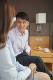 Business couple smiling and sitting on bed in hotel room Royalty Free Stock Images