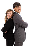 Business couple standing back to back smiling at the camera Stock Image
